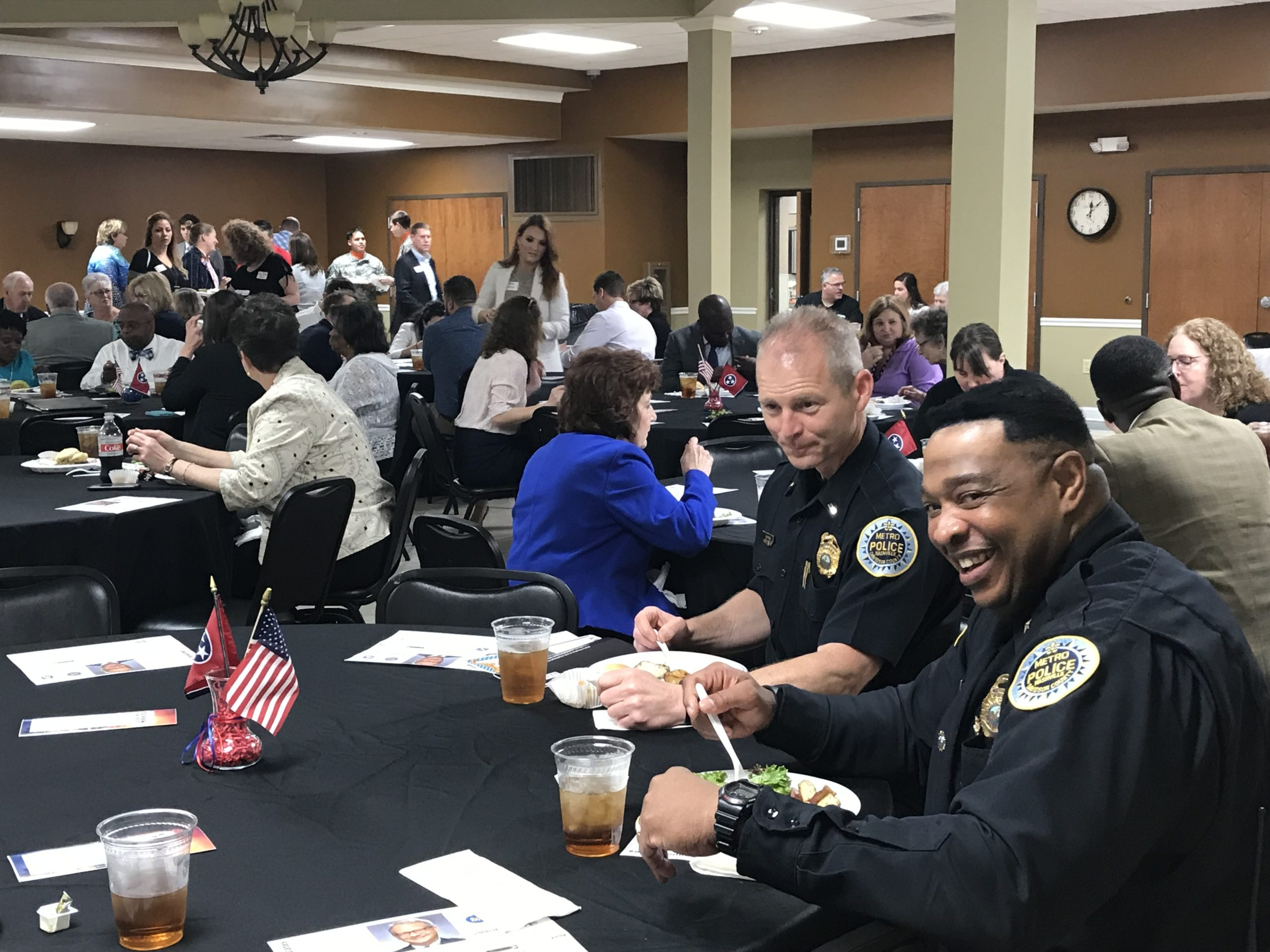 Several groupd sit at tables for the luncheon, including two members of local police enjoying a meal.