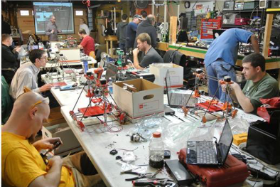 A group of men work on engineering projects in some of the existing buildings