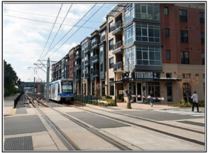 A street with a metro public tram line going by rosa of apartments and shops.