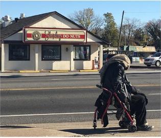 A homeless man on a wheelchair on a corner.